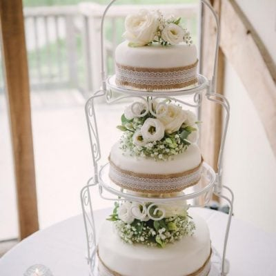 The wedding cake decorated with white and green flowers. We love the lace decor.